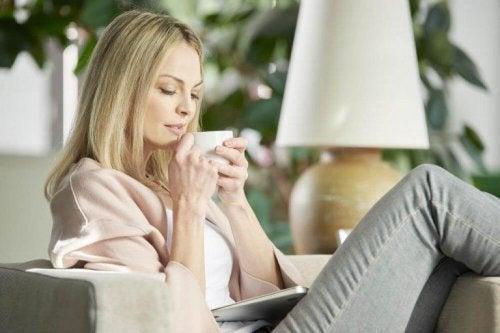 Eine Frau sitzt auf einer Couch und trinkt Tee.