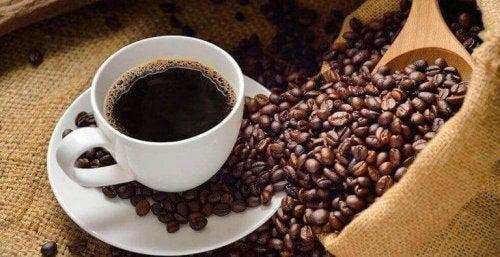 Eine Tasse Kaffee und daneben liegen viele Kaffeebohnen.