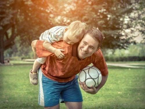 Vater und Sohn spielen mit einem Fußball.