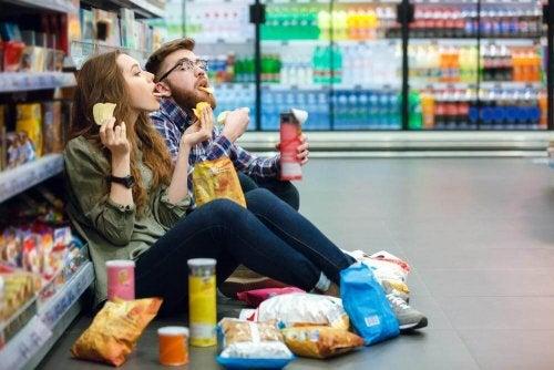 Pärchen futtert ungesunde Snacks im Supermarkt