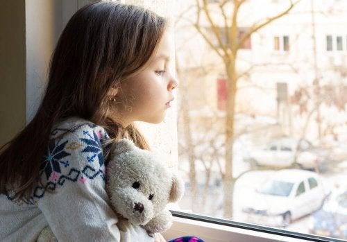 Trauriges Kind schaut aus dem Fenster