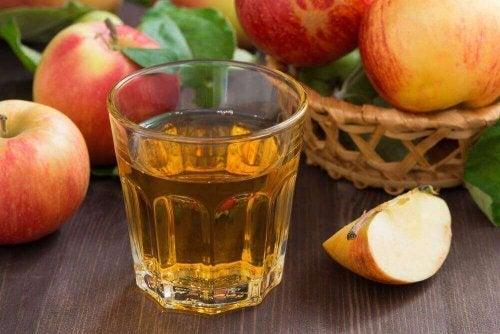 Ein Glas Apfelwasser, neben dem einige Äpfel liegen.