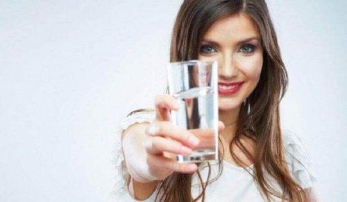 Eine Frau hält ein Glas Wasser mit ausgestreckter Hand.
