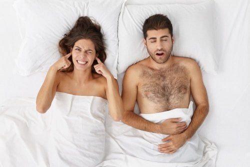 Frau liegt mit schnarchendem Mann im Bett