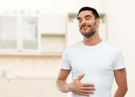 Ein Mann hält sich lächelnd den Bauch, da ihm Wermut bei der Verdauung geholfen hat.