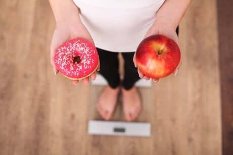 Frau steht auf der Waage mit Apfel und Donut in der Hand