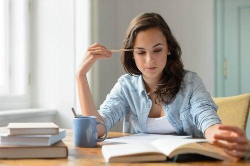 Junge Frau sitzt am Tisch und lernt