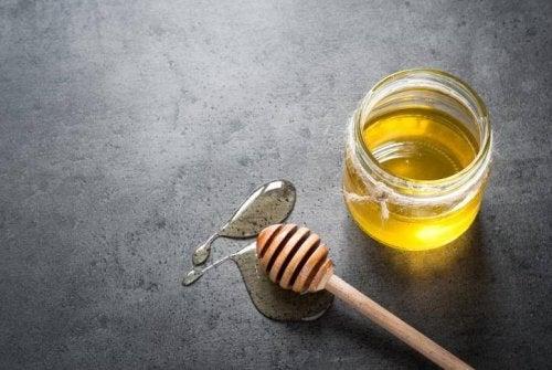 Ein Glas Honig mit Holzlöffel