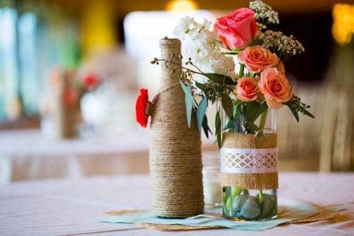 Flaschen mit Blumen als Tischdekoration