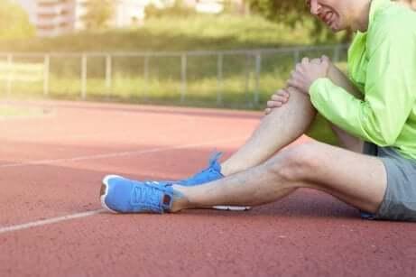 Sportler sitzt auf Aschenbahn und hält sein Knie