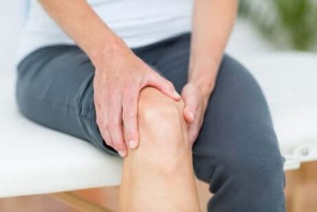 Zwei Hände halten ein schmerzendes Knie