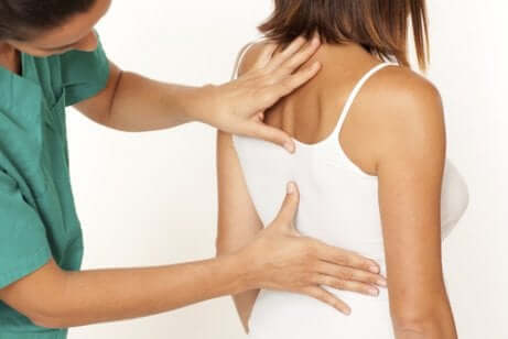 Arzt untersucht die Wirbelsäule einer Frau