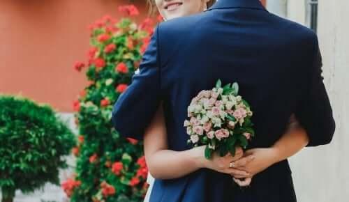 Brautpaar-umarmt-mit-Blumenstrauß