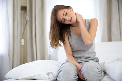 Frau mit Nackenschmerzen sitzt auf dem Bett