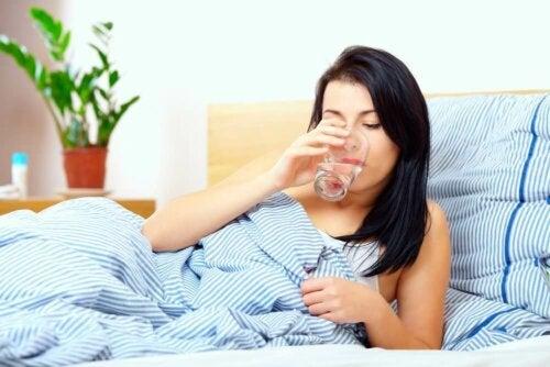Frau trinkt Wasser gegen Schleim im Rachen
