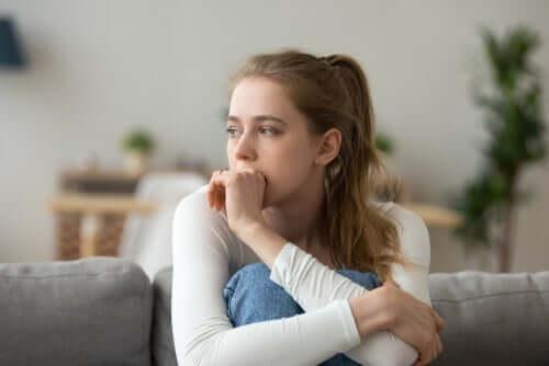 Frau enstpannt sich auf Sofa und betreibt Nesting