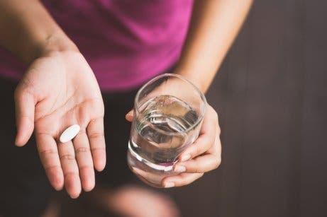 Person mit Paracetamol und einem Glas Wasser in der Hand