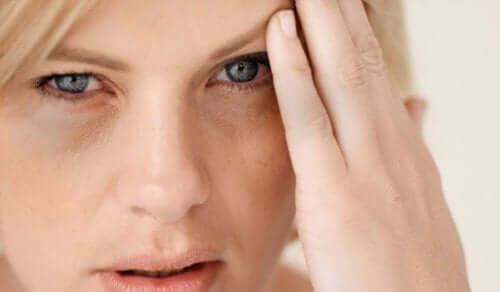Herzinfarktsymptome - Frau mit Kopfschmerzen