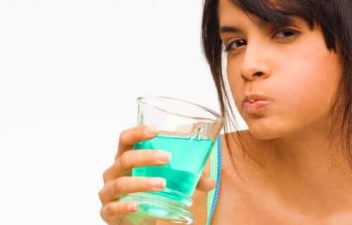 Frau verwendet Mundspülung mit Chlorhexidin