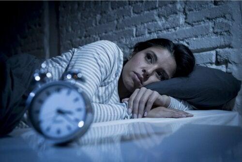 Frau im Bett schaut auf Uhr schlaflos