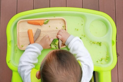 Kind spielt mit Babynahrung