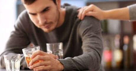 Alkoholiker trinkt mit der Hand einer Person auf seiner Schulter