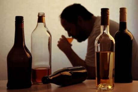 Ein Alkoholiker beim Trinken mit mehreren Flaschen