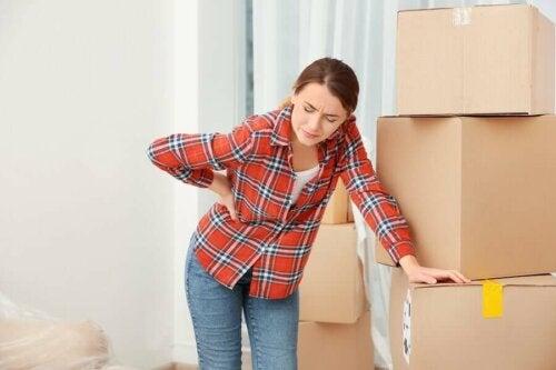 Frau hebt schwere Kisten