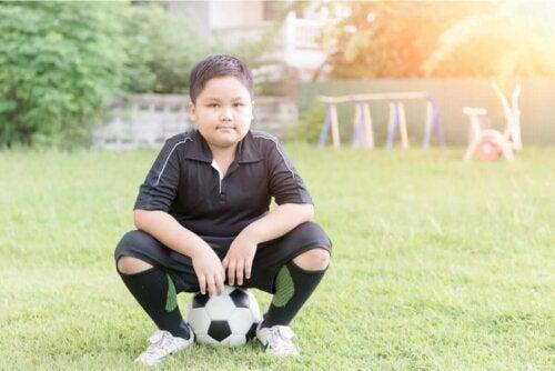 Kindern beibringen - Junge sitzt auf einem Fußball