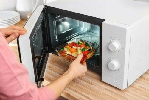 Kunststoff in der Mikrowelle - Frau stellt Glasbehälter in Mikrowelle