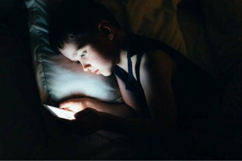 Soziale Medien - Kind nutzt Handy unter der Bettdecke