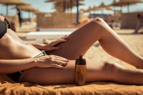Eine Frau, die am Strand liegt und eine Flasche Bräunungsöl neben sich stehen hat