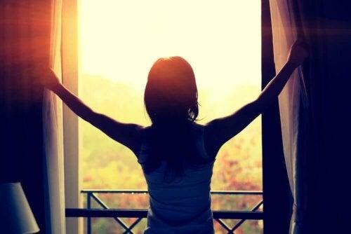 Eine Frau, die an einem sonnigen Tag die Vorhänge öffnet
