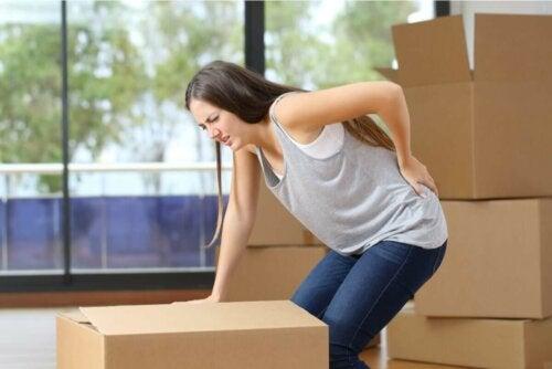Eine Frau mit Schmerzen im unteren Rücken vom Heben einer schweren Kiste