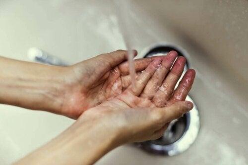 Eine Frau wäscht sich die Hände unter dem Wasserhahn