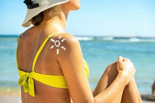 Eine Frau sitzt am Strand mit einer Sonne aus Sonnencreme auf der Schulter