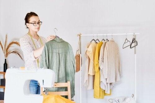 Eine Frau, die Kleidung auf ein Gestell hängt, mit einer Nähmaschine im Vordergrund