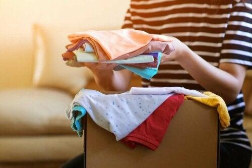 Eine Frau sortiert eine Kiste mit gespendeter Kleidung