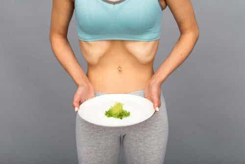 Diabulimie-extrem dünne Frau hält Teller mit einem Stück Salat.