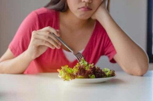 Abnehmen, ohne zu hungern - Frau isst lustlos einen Salat
