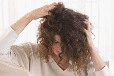 Haarausfall in der Stillzeit - Frau fasst sich in die Haare