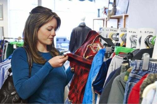 gebrauchte Kleidung kaufen - Frau überprüft ein Kleidungsstück